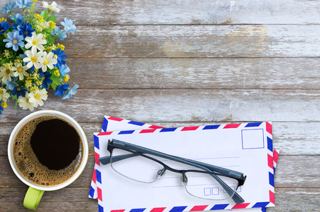 Top view with air mail envelope, cup of coffee, glasses and flower on wood table