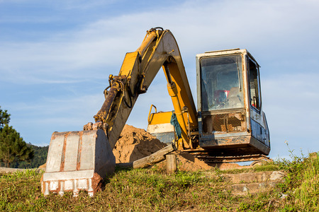 Large construction excavator of yellow color on the construction site with blue sky 스톡 콘텐츠