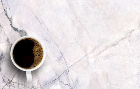 Morning black coffee in white cup on white marble background. Top view with copy space.