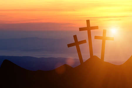 Jesus Christ cross on a background with dramatic sky, lighting, colorful red, orange sunset, dark clouds, sunbeams, sun rays glowing behind the three wooden crosses on Golgotha mountain.Easter, resurrection, Good Friday concept.