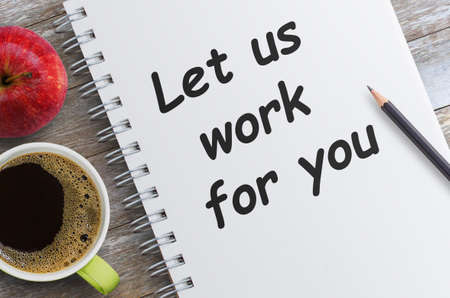 Text Let us work for you on notebook page with cup of coffee, pencil and red apples on wooden table in office workspace.