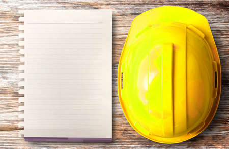 Top view of yellow safety helmet hat and blank paper in the project at construction site building on wood table background. helmet for workman as engineer worker. concept safety first