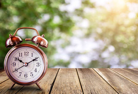 Retro alarm clock on a wooden table with blured bokeh background. Save time savings daylight up retro waking school. Daylight time nap hour decoration late save