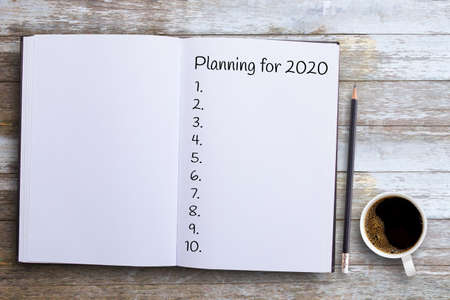 Top view, Plan for 2020 word on notebook with pencil on wooden table and cup of coffee on wood table background or office desk background. Business concept Stock Photo