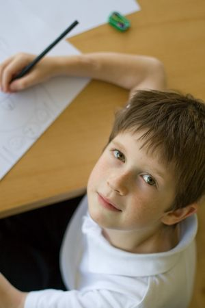 Boy at a table doing homeworkdrawing, high angle view Stock Photo