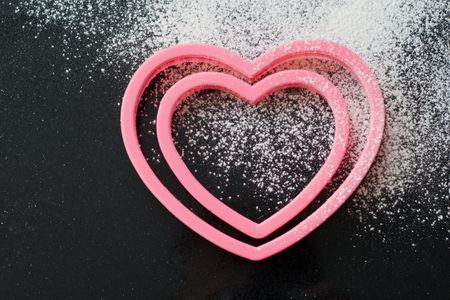 worktop: Two heart shaped cookie cutters on a granite worktop, with a dusting of icing sugar