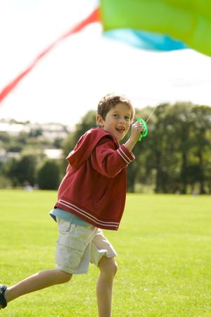Boy running and laughing with a kite photo