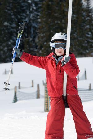 Smiling boy on a ski lift carrying ski poles photo