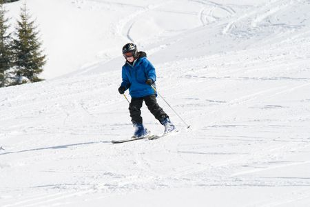 seaonal: Boy skiing down a snowy slope on a sunny day