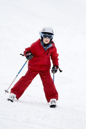 seaonal: Smiling young boy skiing down a snowy slope Stock Photo