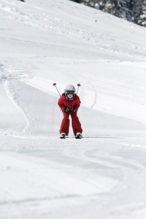 seaonal: Young boy skiing down a slope, ski poles tucked under his arms
