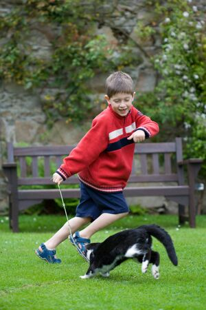 Young boy laughing and chasing his pet cat