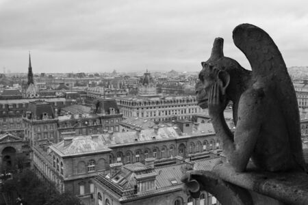 brooding: Gargoyle on Notre Dame overlooking Paris on a cloudy day