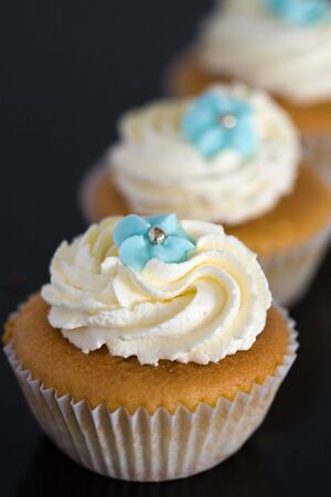 piped: Cupcakes decorated with whipped cream and blue sugar flowers