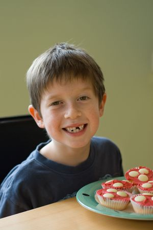 Boy with gap-tooth smile and cupcakes Stock Photo - 3252646