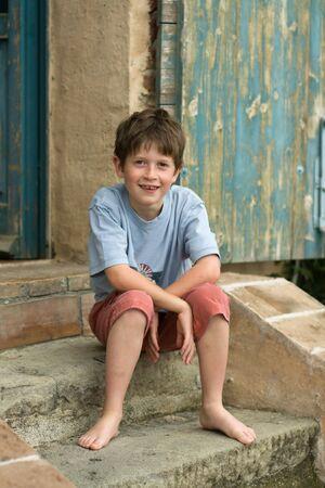 piedi nudi ragazzo: Ragazzo sorridente seduto su passi Archivio Fotografico