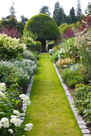 shrubs: Beautiful lawned pathway surrounded by flower borders Stock Photo