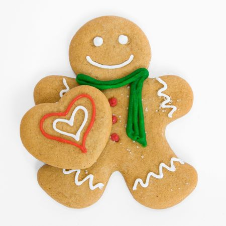 ingefära: Smiling gingerbread man holds iced gingerbread heart Stockfoto