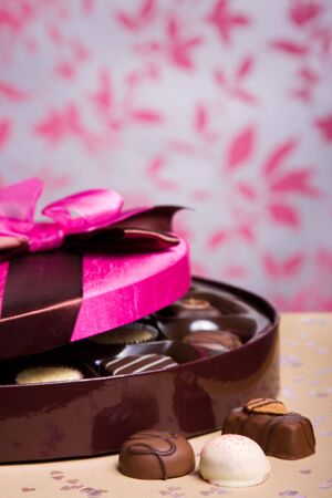 box of chocolates: Luxury chocolates in a box with pink satin lid, shallow depth of field with focus on chocolates at front