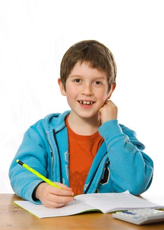 Happy young boy smiling whilst doing homework photo