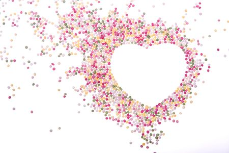 Heart shaped frame made from colored sprinkles photo