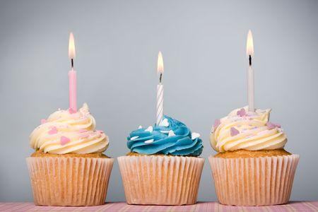 Tr�o de frosting cupcakes decoradas con velas y