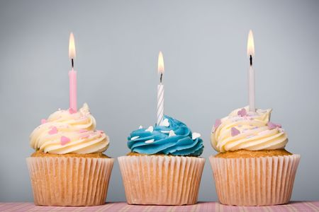 three: Trio of cupcakes decorated with frosting and candles Stock Photo