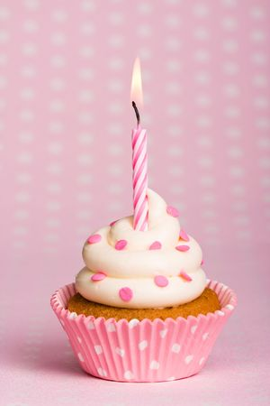 Spotty pink cupcake with a stripey candle photo