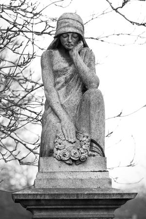 adorning: Statue adorning the top of a gravestone