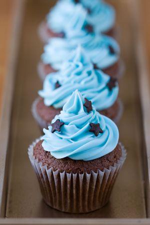 Fila en miniatura de chocolate cupcakes decoradas con estrellas Foto de archivo
