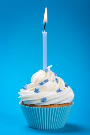 first birthday: Cupcake with a single blue candle, decorated with sugar stars Stock Photo
