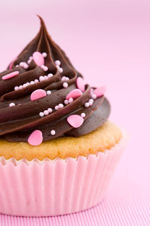 Pink chocolate cupcake against a pink background photo
