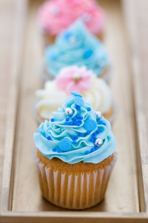 Pink and blue cupcakes arranged on a tray