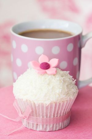tarde de cafe: Cupcake decorado con coco dessicated y una flor de az�car Foto de archivo