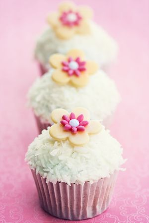 Cupcakes decorated with dessicated coconut and sugar flowers photo