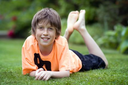 preteen boy: Boy relaxing on the lawn