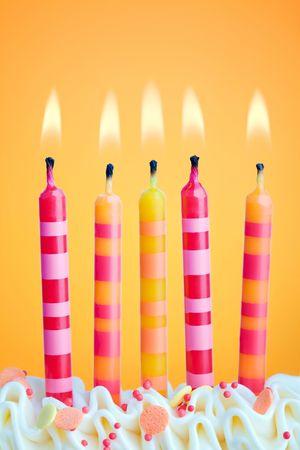 geburtstagskerzen: F�nf Geburtstagskerzen gegen einen orangefarbenen Hintergrund