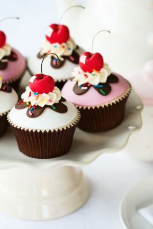 Cherry cupcakes on a cake stand photo