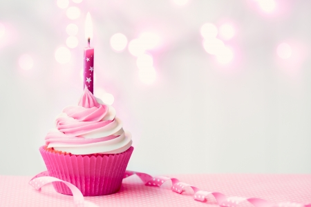 candle lights: Pink birthday cupcake Stock Photo