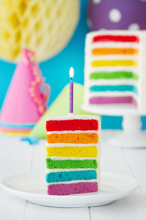 Rainbow cake decorated with a single candle photo