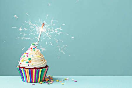kerze: Cupcake mit bunten Streuseln und Wunderkerzen dekoriert Lizenzfreie Bilder