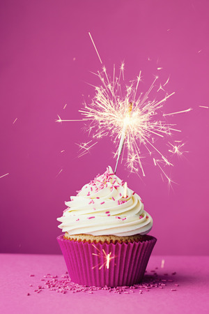 Birthday cupcake with a sparkler against a pink background photo