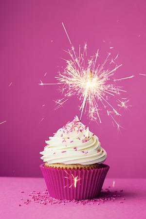 Magdalena del cumpleaños con una bengala contra un fondo de color rosa Foto de archivo