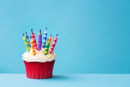 torta compleanno: Cupcake compleanno con le candele soffiata fuori contro uno sfondo blu