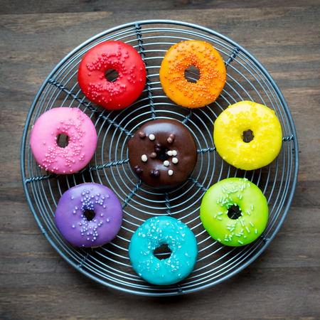 Colorful glazed donuts on a wire rack photo
