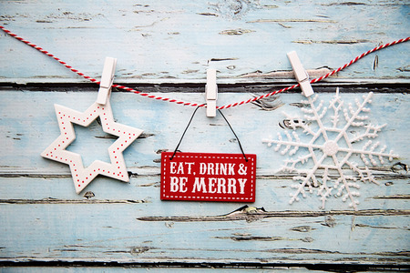 seasonal clothes: Eat, drink and be merry sign against a distressed wooden background