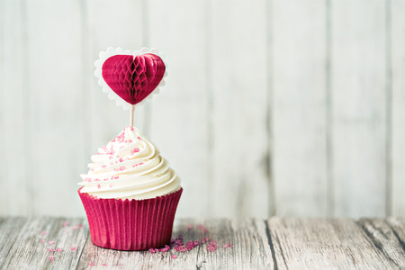 Cupcake decorated with a heart shaped cake pick 스톡 콘텐츠