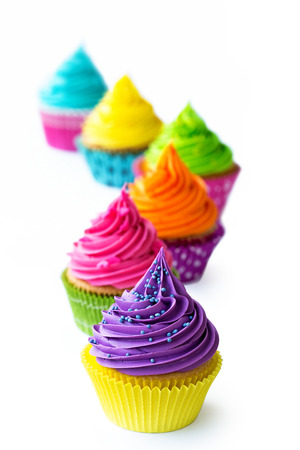 Row of colorful cupcakes against white