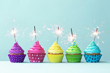 pastel: Fila de pastelitos de colores con luces de bengala