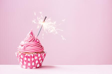 gateau anniversaire: Petit g�teau rose orn� d'une sparkler